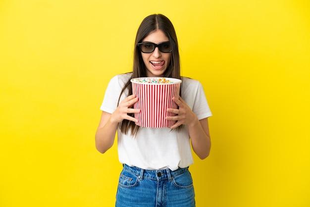 Jonge blanke vrouw geïsoleerd op gele achtergrond met 3d-bril en met een grote emmer popcorns