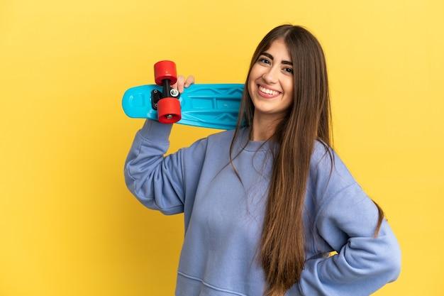 Jonge blanke vrouw geïsoleerd op gele achtergrond met een skate met gelukkige expressie