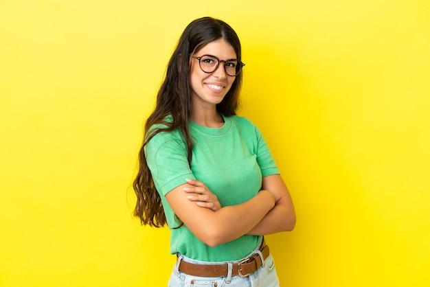 Jonge blanke vrouw geïsoleerd op gele achtergrond met gekruiste armen en vooruitkijkend