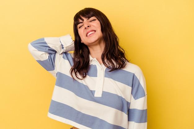 Jonge blanke vrouw geïsoleerd op gele achtergrond met nekpijn als gevolg van stress, masseren en aanraken met de hand.