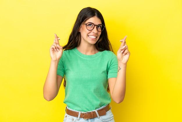 Jonge blanke vrouw geïsoleerd op gele achtergrond met vingers die kruisen en het beste wensen