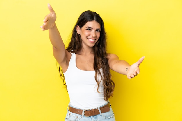 Jonge blanke vrouw geïsoleerd op gele achtergrond presenteren en uitnodigen om met de hand te komen