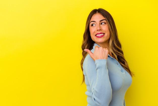 Jonge blanke vrouw geïsoleerd op gele achtergrond punten met duim vinger weg, lachend en zorgeloos.