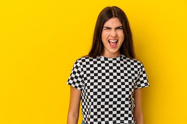 Jonge blanke vrouw geïsoleerd op gele achtergrond schreeuwen erg boos, woede concept, gefrustreerd.