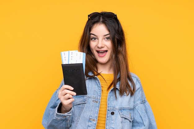 Jonge blanke vrouw geïsoleerd op gele muur gelukkig in vakantie met paspoort en vliegtickets