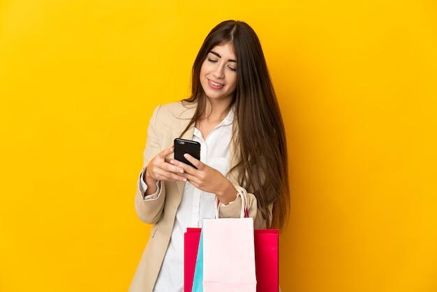 Jonge blanke vrouw geïsoleerd op gele muur met boodschappentassen en een bericht schrijven met haar mobiele telefoon naar een vriend