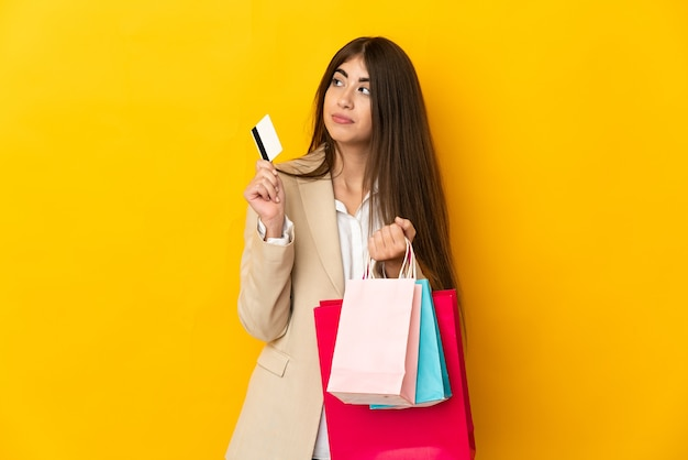 Jonge blanke vrouw geïsoleerd op gele muur met boodschappentassen en een creditcard en denken