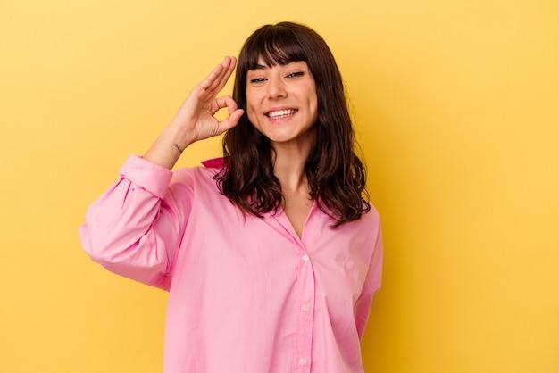 Jonge blanke vrouw geïsoleerd op gele muur vrolijk en zelfverzekerd tonend ok gebaar.