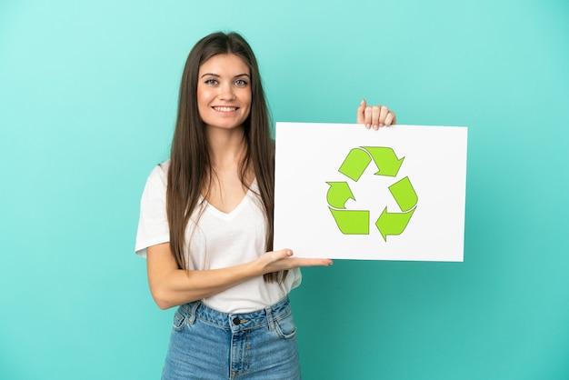 Jonge blanke vrouw geïsoleerd op het houden van een bordje met recycle icoon met gelukkige uitdrukking