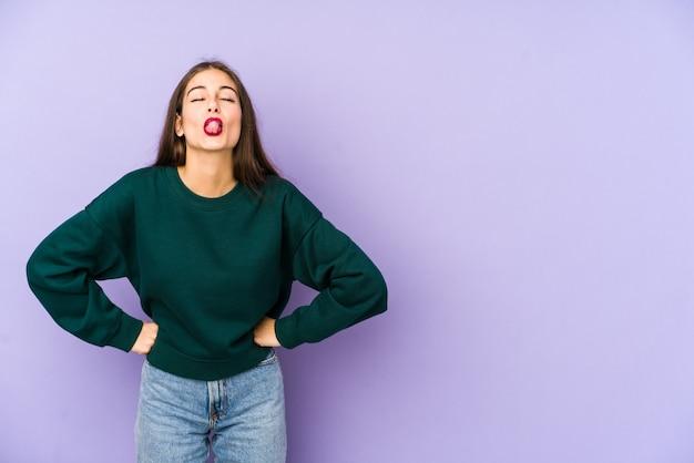 Jonge blanke vrouw geïsoleerd op paars grappig en vriendelijk tong uitsteekt.