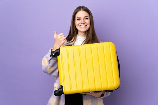 Jonge blanke vrouw geïsoleerd op paars in vakantie met reiskoffer en met duim omhoog