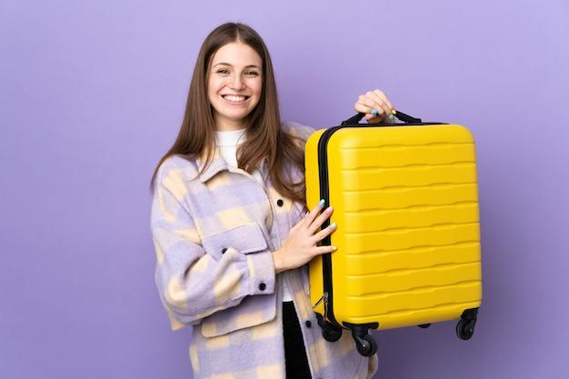 Jonge blanke vrouw geïsoleerd op paars in vakantie met reiskoffer
