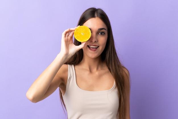 Jonge blanke vrouw geïsoleerd op paars met een sinaasappel