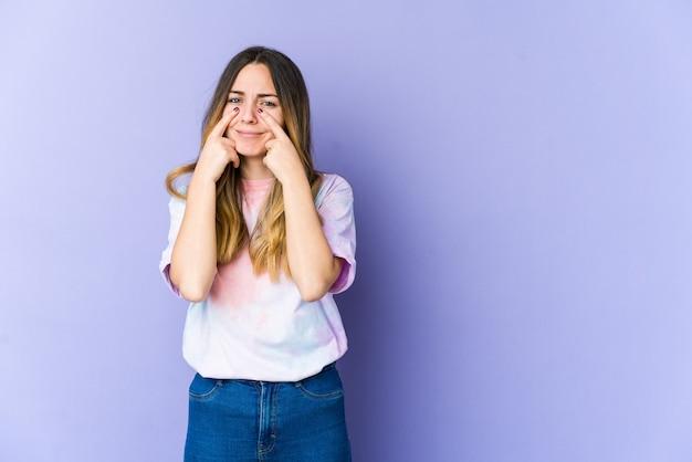 Jonge blanke vrouw geïsoleerd op paarse achtergrond huilen, ongelukkig met iets, pijn en verwarring concept.