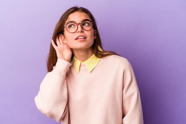 Jonge blanke vrouw geïsoleerd op paarse achtergrond probeert te luisteren naar een roddel.