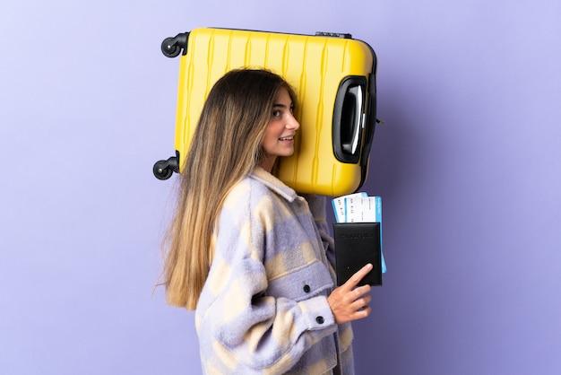 Jonge blanke vrouw geïsoleerd op paarse muur in vakantie met koffer en paspoort