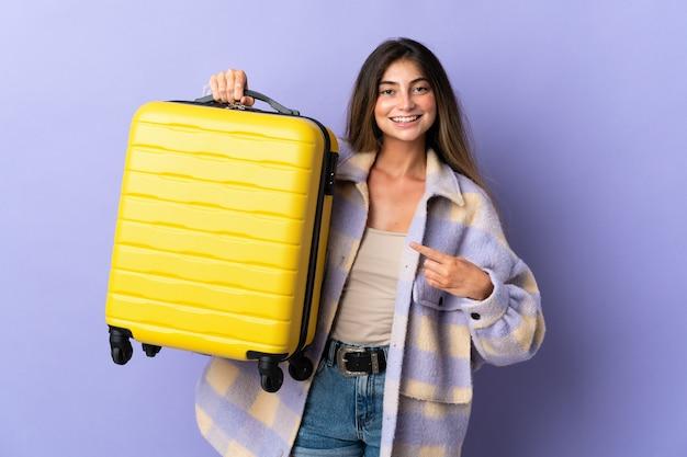 Jonge blanke vrouw geïsoleerd op paarse muur in vakantie met reiskoffer