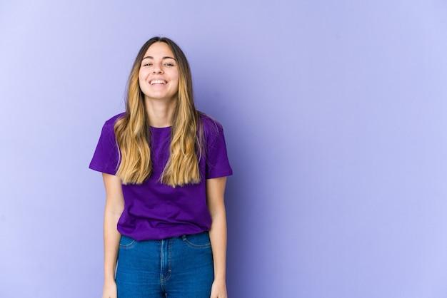 Jonge blanke vrouw geïsoleerd op paarse muur lacht en sluit de ogen, voelt zich ontspannen en gelukkig.