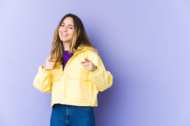 Jonge blanke vrouw geïsoleerd op paarse muur vrolijke glimlachen naar voren wijzen.