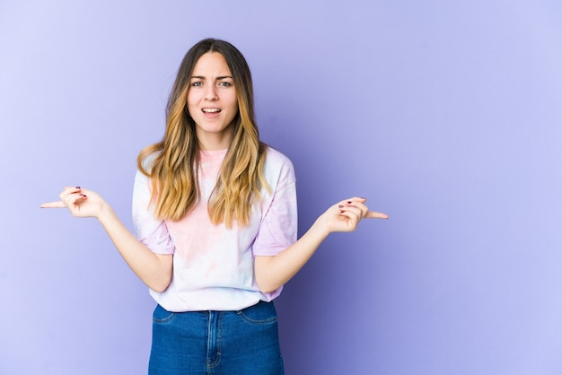 Jonge blanke vrouw geïsoleerd op paarse muur wijzend naar verschillende kopie ruimtes, het kiezen van een van hen, tonen met vinger.
