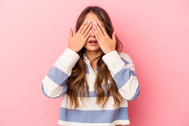 Jonge blanke vrouw geïsoleerd op roze achtergrond bang voor ogen met handen.