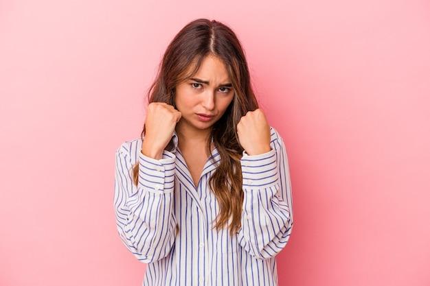 Jonge blanke vrouw geïsoleerd op roze achtergrond boos schreeuwen met gespannen handen.
