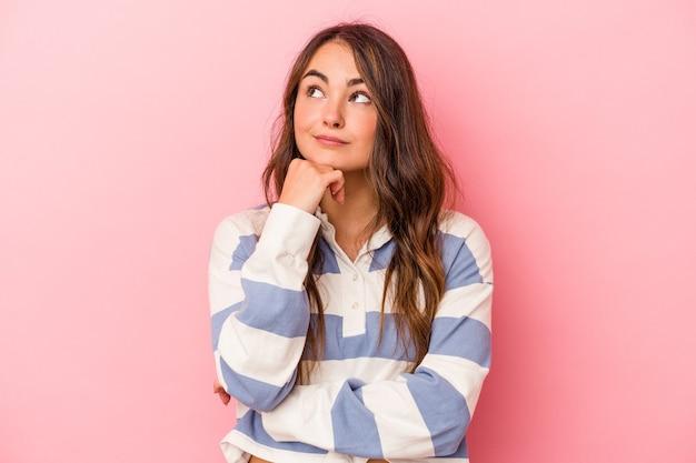 Jonge blanke vrouw geïsoleerd op roze achtergrond denken en opzoeken, reflecterend zijn, nadenken, een fantasie hebben.