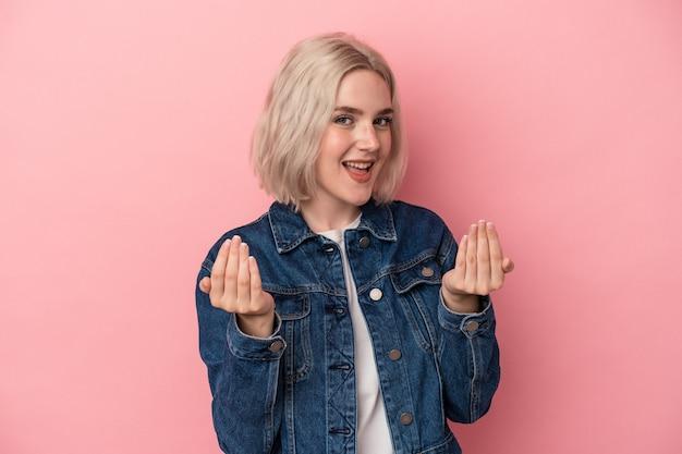 Jonge blanke vrouw geïsoleerd op roze achtergrond die met de vinger naar je wijst alsof uitnodigend dichterbij komt.
