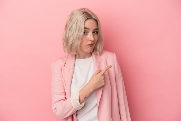 Jonge blanke vrouw geïsoleerd op roze achtergrond glimlachend en opzij wijzend, iets tonen op lege ruimte.
