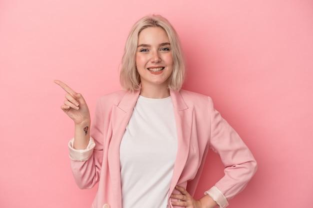 Jonge blanke vrouw geïsoleerd op roze achtergrond glimlachend vrolijk wijzend met wijsvinger weg.