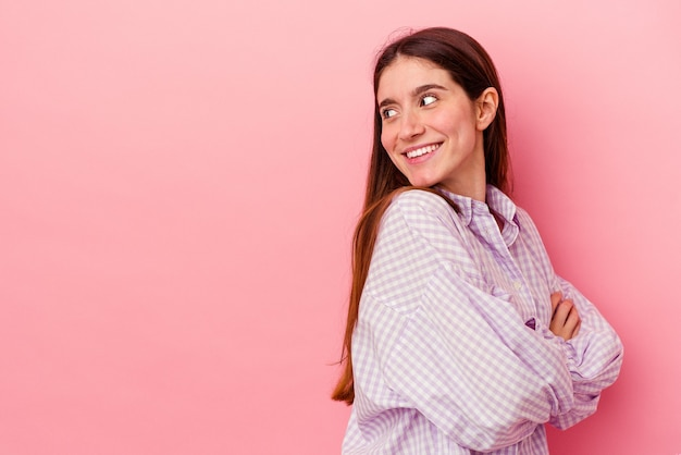 Jonge blanke vrouw geïsoleerd op roze achtergrond glimlachend zelfverzekerd met gekruiste armen.