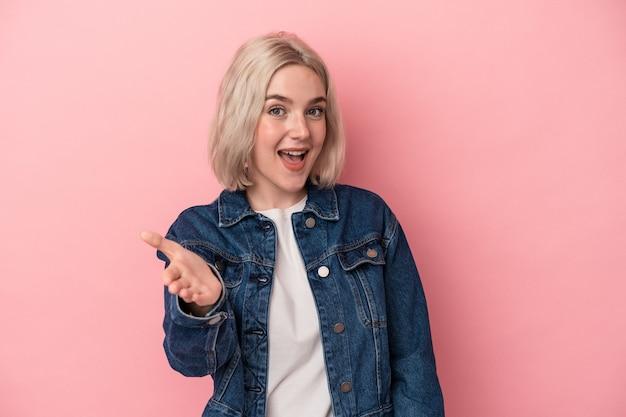 Jonge blanke vrouw geïsoleerd op roze achtergrond hand uitrekken op camera in begroeting gebaar.