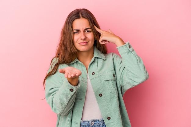 Jonge blanke vrouw geïsoleerd op roze achtergrond houden en tonen van een product bij de hand.