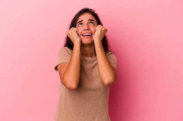 Jonge blanke vrouw geïsoleerd op roze achtergrond huilen, ongelukkig met iets, pijn en verwarring concept.