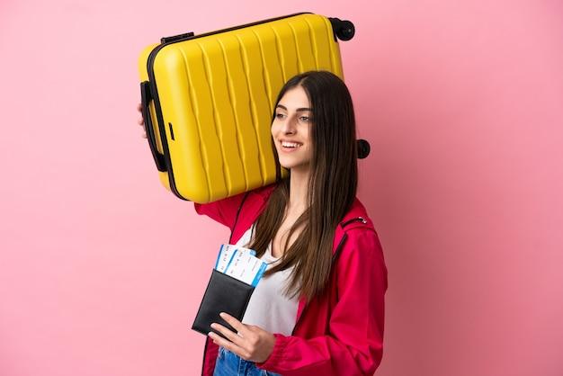 Jonge blanke vrouw geïsoleerd op roze achtergrond in vakantie met koffer en paspoort