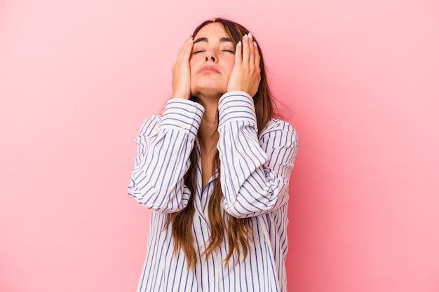 Jonge blanke vrouw geïsoleerd op roze achtergrond jammerend en huilend troosteloos.