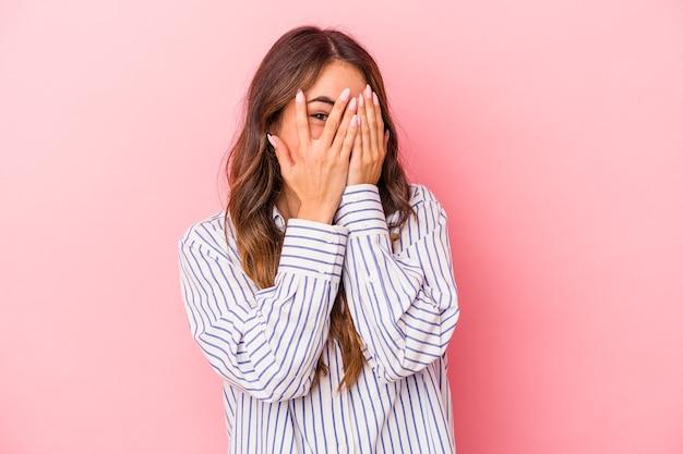 Jonge blanke vrouw geïsoleerd op roze achtergrond knippert naar de camera door vingers, beschaamd bedekkend gezicht.