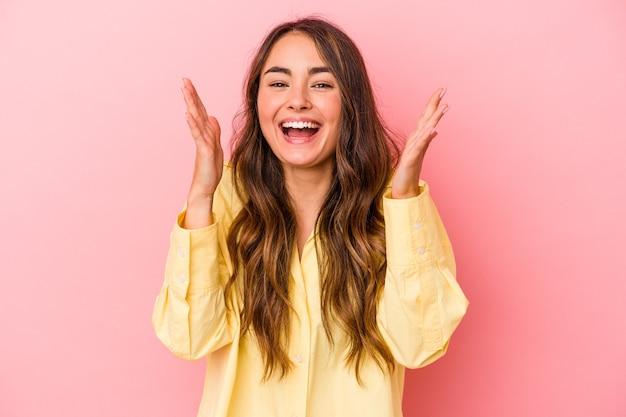 Jonge blanke vrouw geïsoleerd op roze achtergrond lacht hardop terwijl ze de hand op de borst houdt.