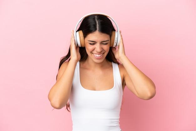 Jonge blanke vrouw geïsoleerd op roze achtergrond luisteren muziek