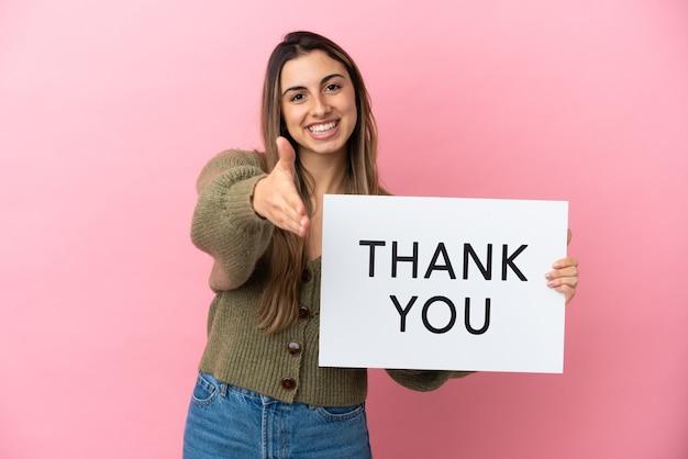 Jonge blanke vrouw geïsoleerd op roze achtergrond met een bordje met de tekst bedankt om een deal te maken
