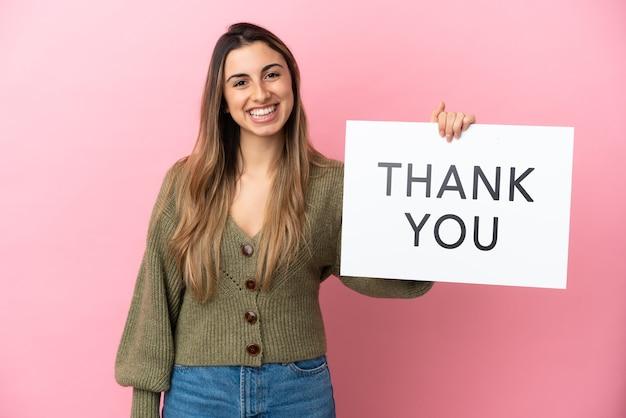 Jonge blanke vrouw geïsoleerd op roze achtergrond met een bordje met tekst bedankt met gelukkige uitdrukking