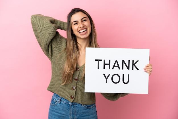 Jonge blanke vrouw geïsoleerd op roze achtergrond met een bordje met tekst dank u en denken