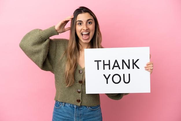 Jonge blanke vrouw geïsoleerd op roze achtergrond met een bordje met tekst dank u met verbaasde uitdrukking