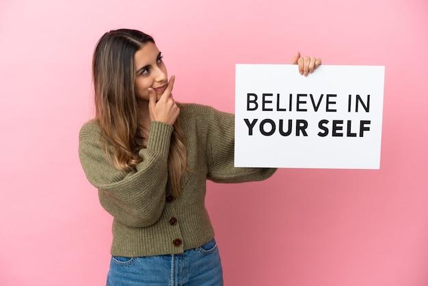 Jonge blanke vrouw geïsoleerd op roze achtergrond met een bordje met tekst geloof in jezelf en denken