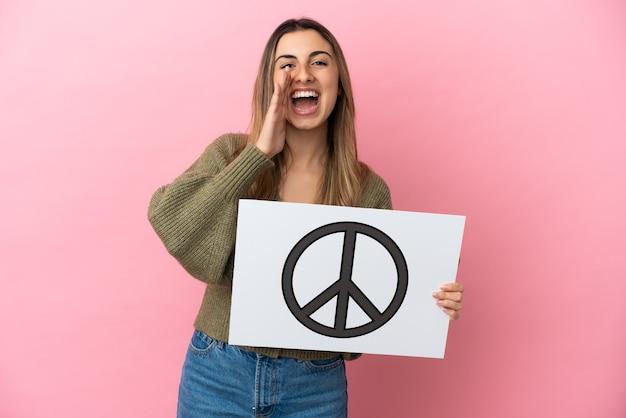 Jonge blanke vrouw geïsoleerd op roze achtergrond met een bordje met vredessymbool en schreeuwen