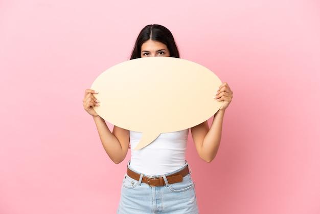 Jonge blanke vrouw geïsoleerd op roze achtergrond met een lege tekstballon die erachter verstopt zit