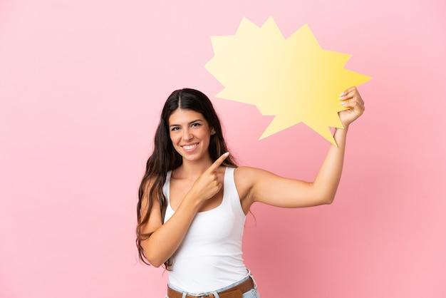 Jonge blanke vrouw geïsoleerd op roze achtergrond met een lege tekstballon en erop wijzend