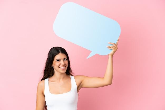 Jonge blanke vrouw geïsoleerd op roze achtergrond met een lege tekstballon
