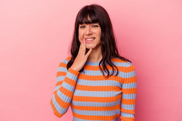 Jonge blanke vrouw geïsoleerd op roze achtergrond met een sterke tandenpijn, kiespijn.