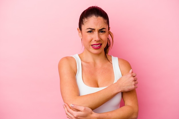 Jonge blanke vrouw geïsoleerd op roze achtergrond met nekpijn als gevolg van stress, masseren en aanraken met de hand.